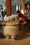 Two children lighting a prayer candle at the Bongeunsa Temple in Seoul by Kelsey Ciagala